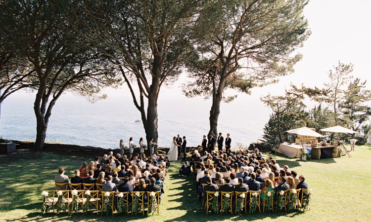outdoor seaside ceremony with ocean trees and grass lawn