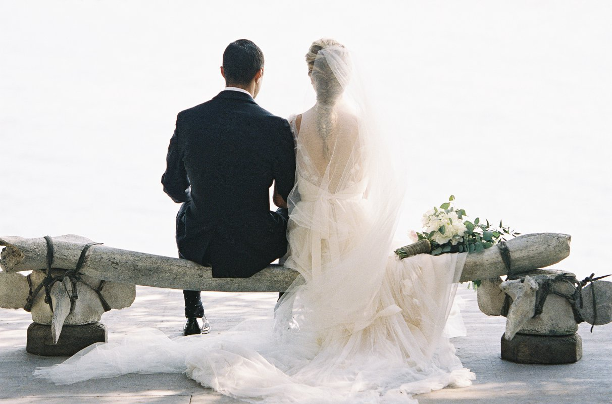 newlyweds sitting on a whale bone bench