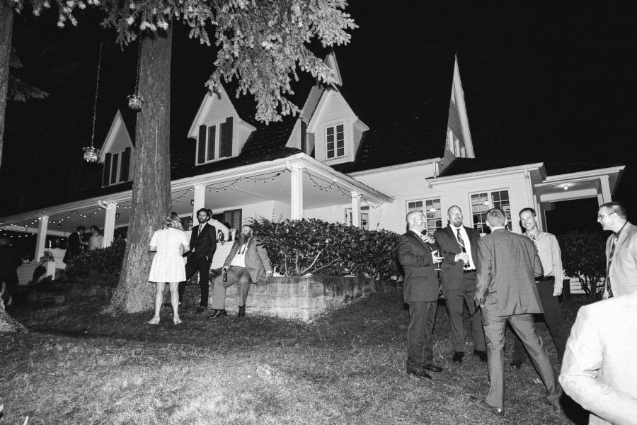 guests standing outside at night