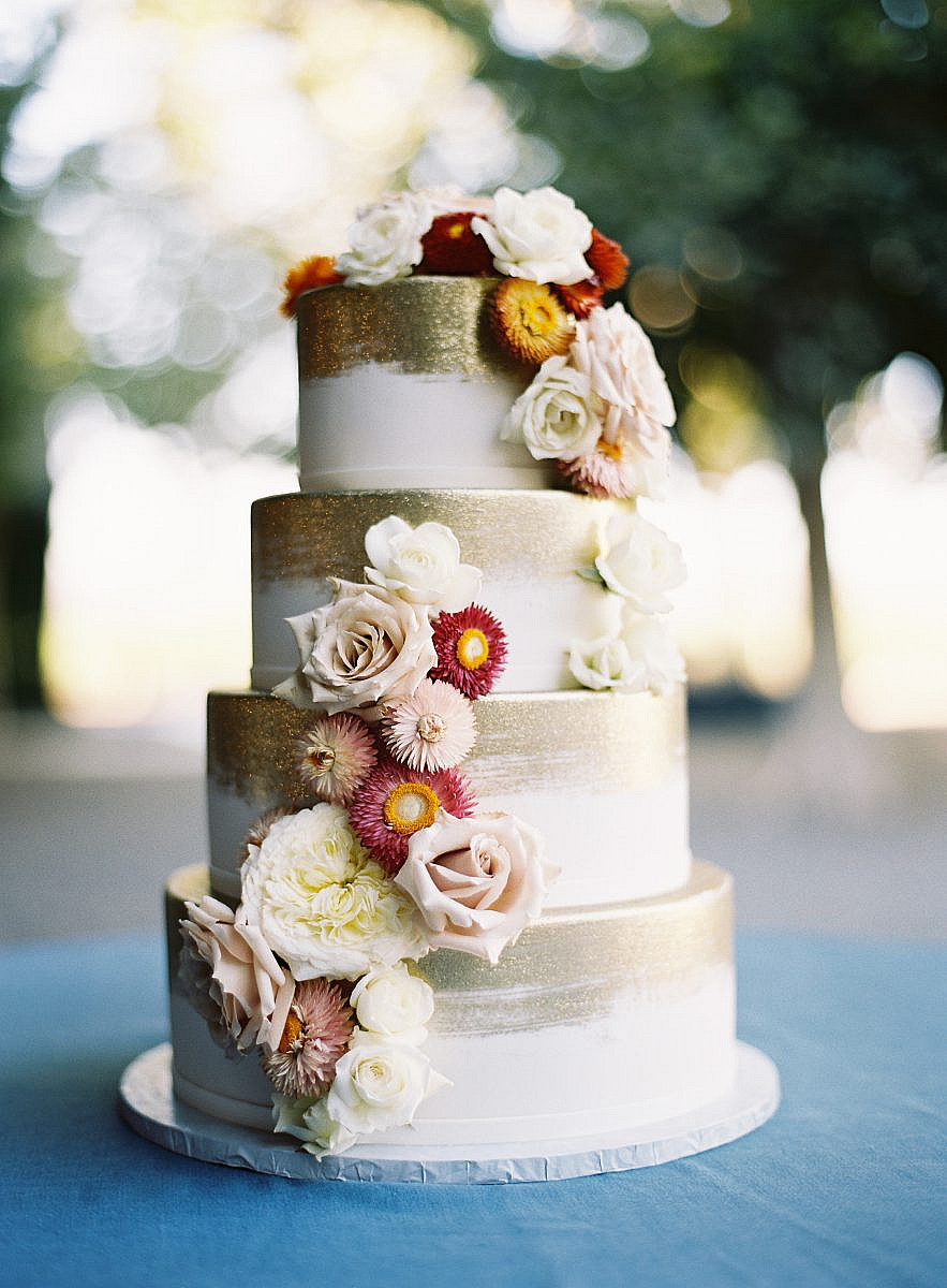 white and gold cake with english daisies and antique white roses