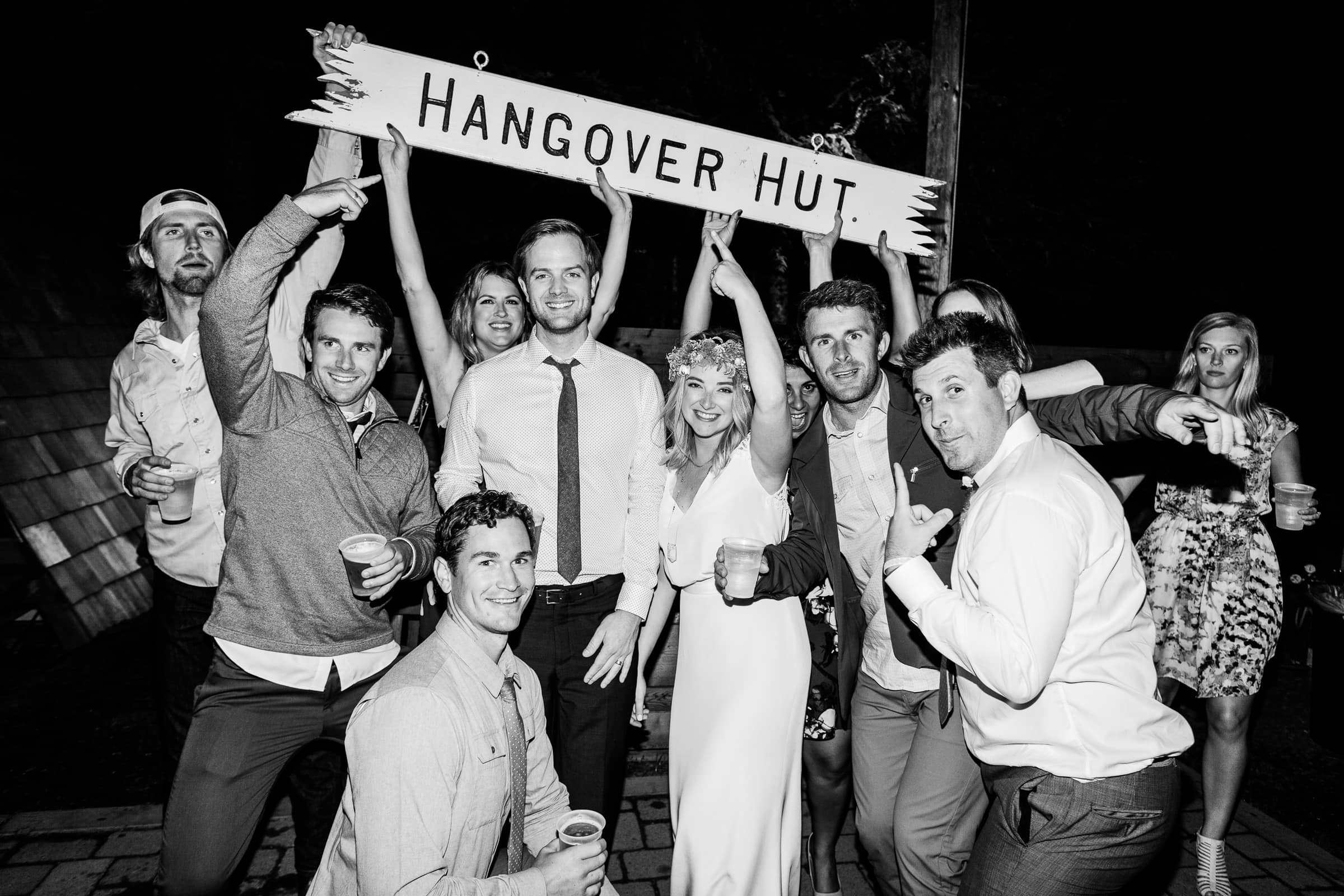 group holding hangover hut sign