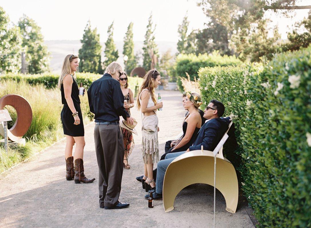 wedding guests mingling in art garden