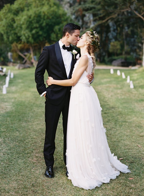 romantic kiss between bride and groom in tuxedo