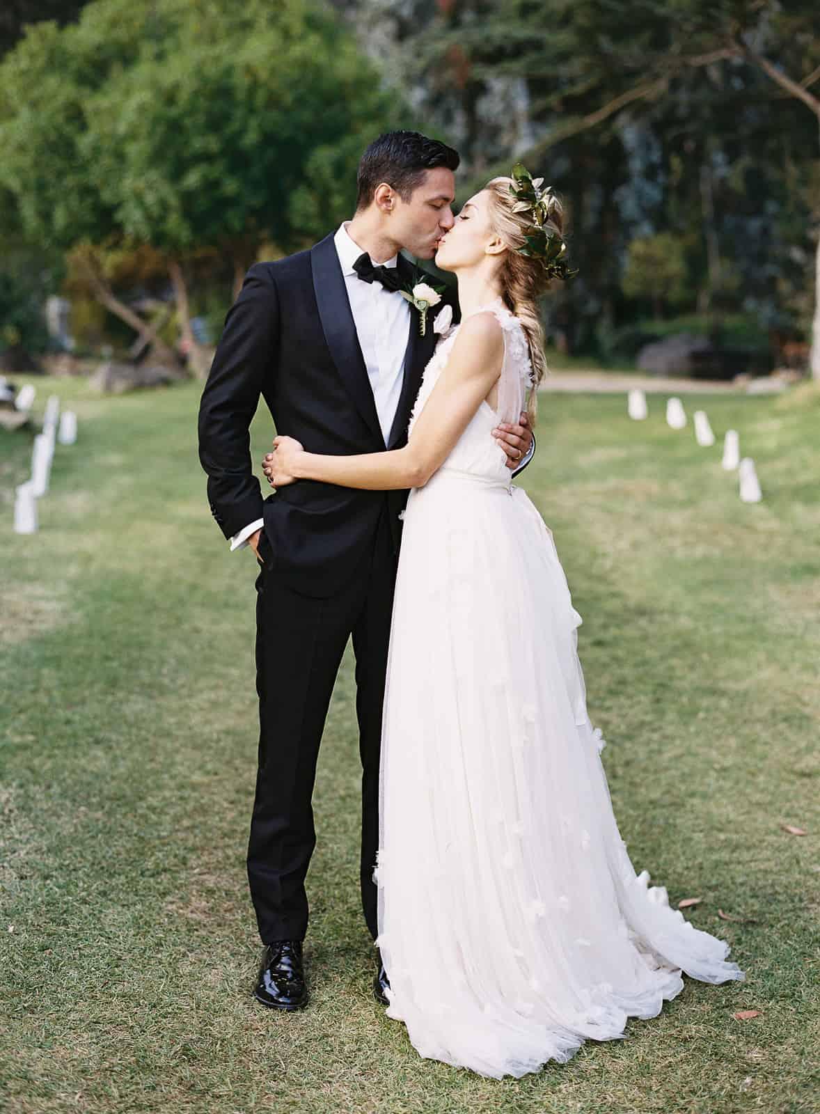 romantic kiss between bride and groom in tuxedo