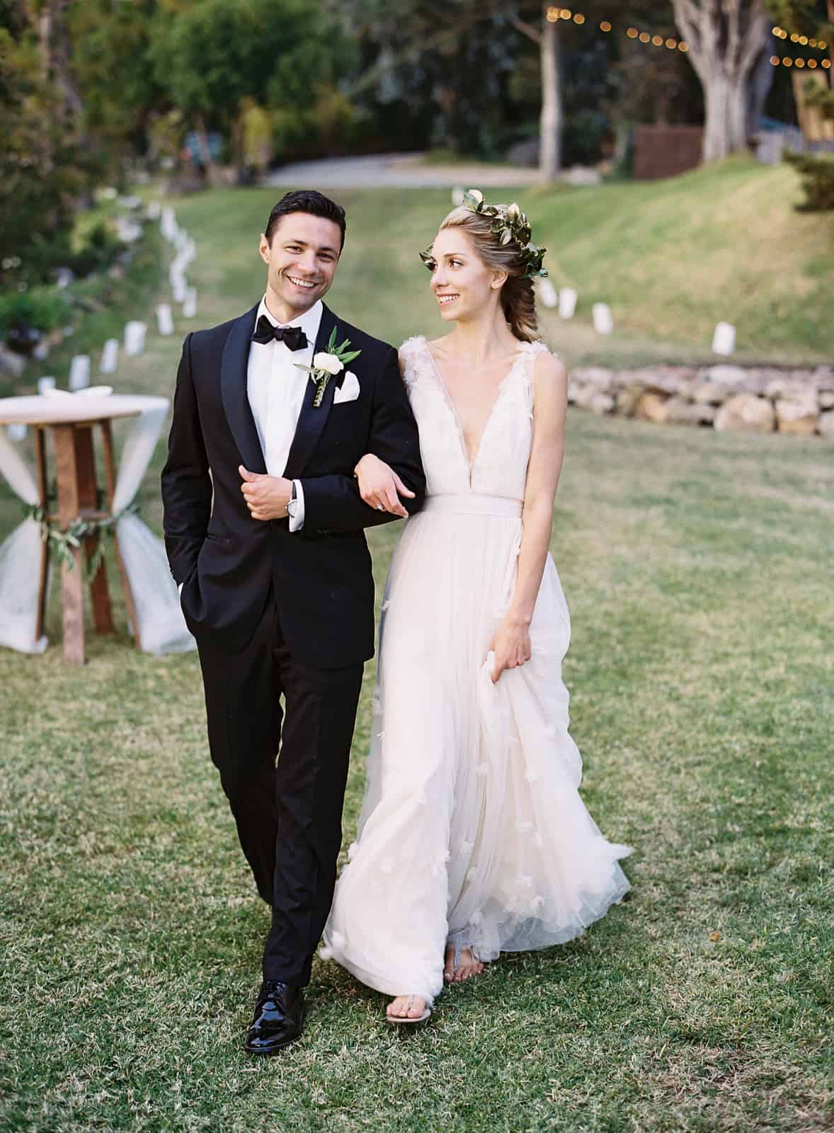 newlyweds walking on grass