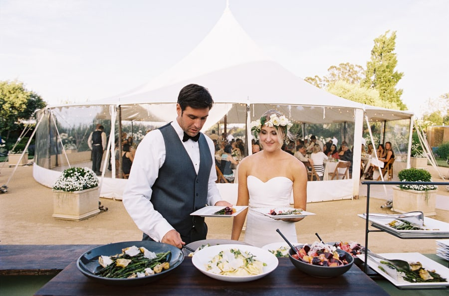 bride and groom at buffet outside white circus tent