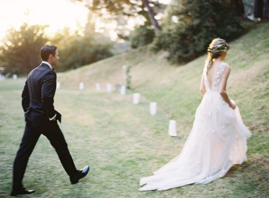 bride and groom walking up a hill