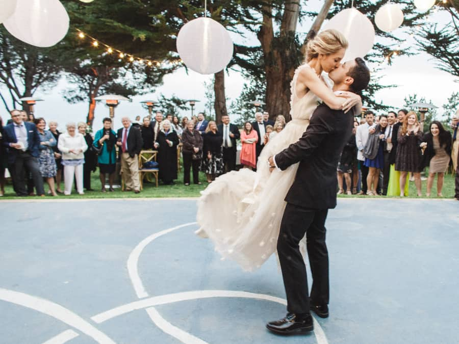 groom picking up bride and kissing her during first dance