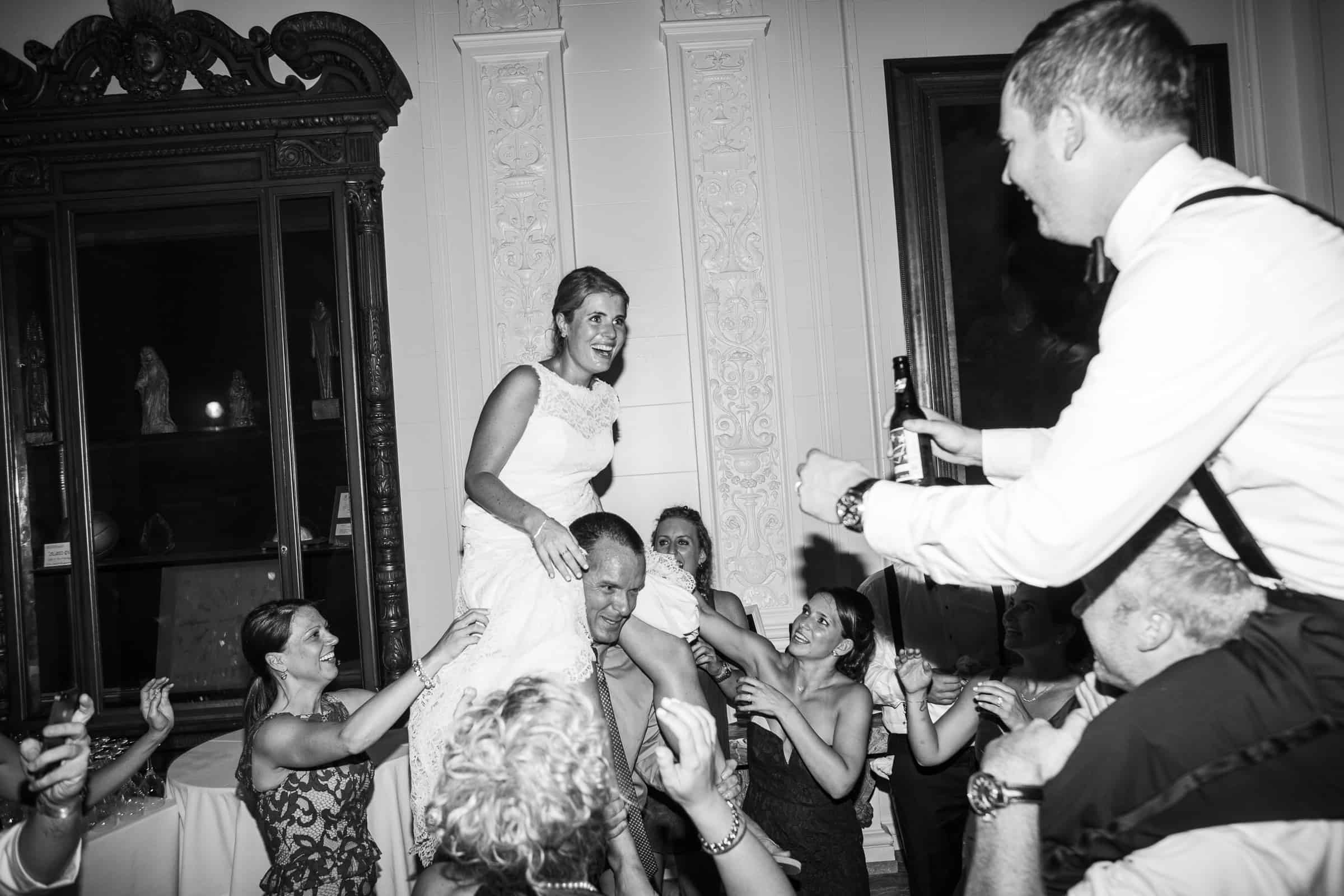 bride and groom on shoulders