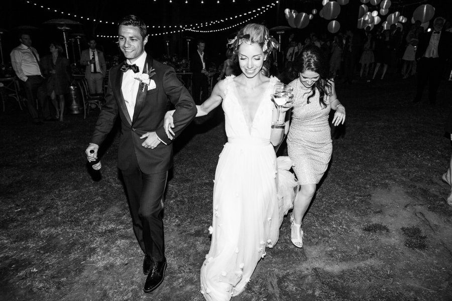 bride groom and bridesmaid walking in the dark holding drinks