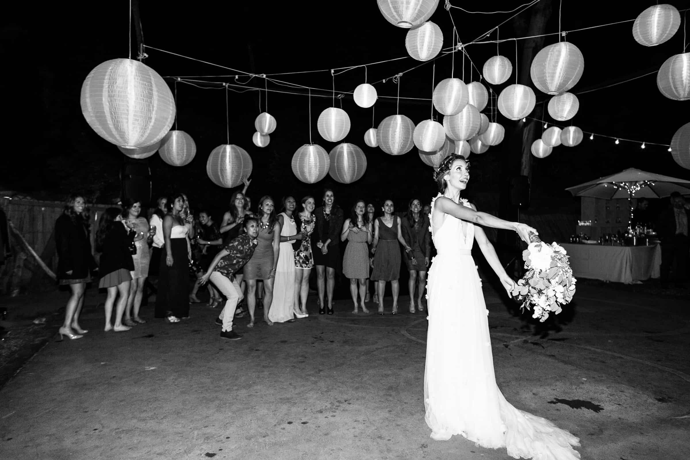 bouquet toss at night with chinese lanterns