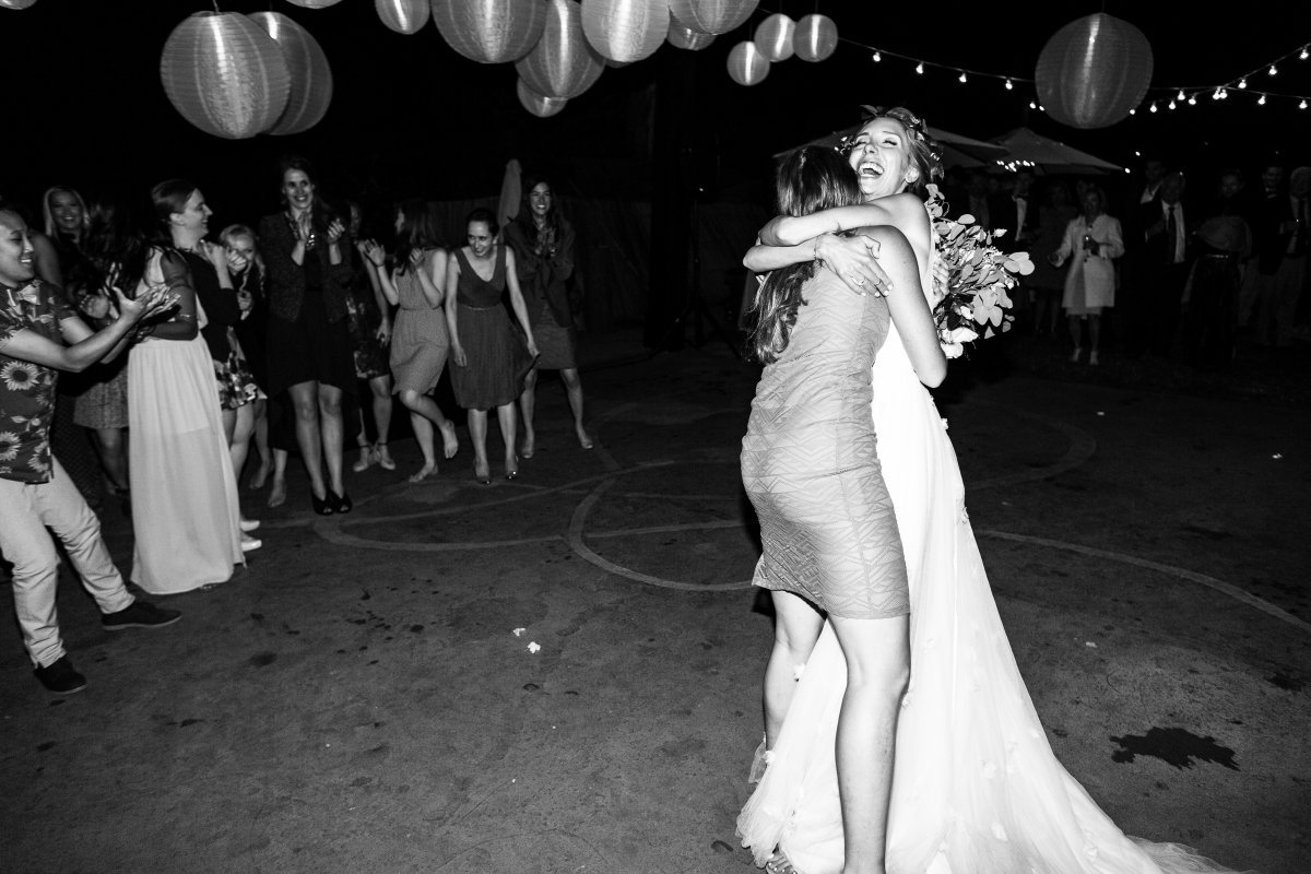 bride hugging girl who caught bouquet