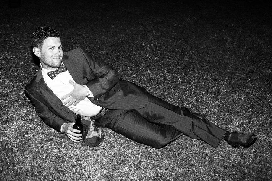man with bow tie lying down in the grass doing funny pose and drinking a beer