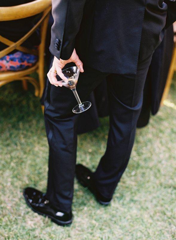 man in tuxedo holding martini glass