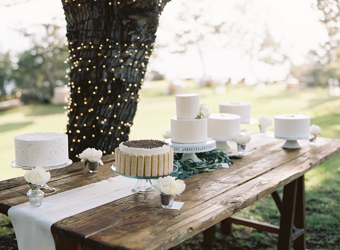 rustic table with assorted white cakes