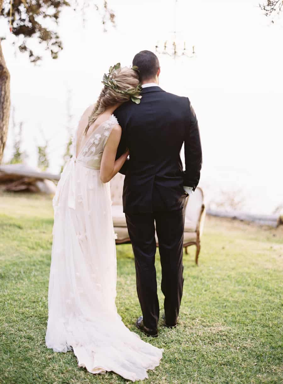 backs of married couple as they look off into the ocean