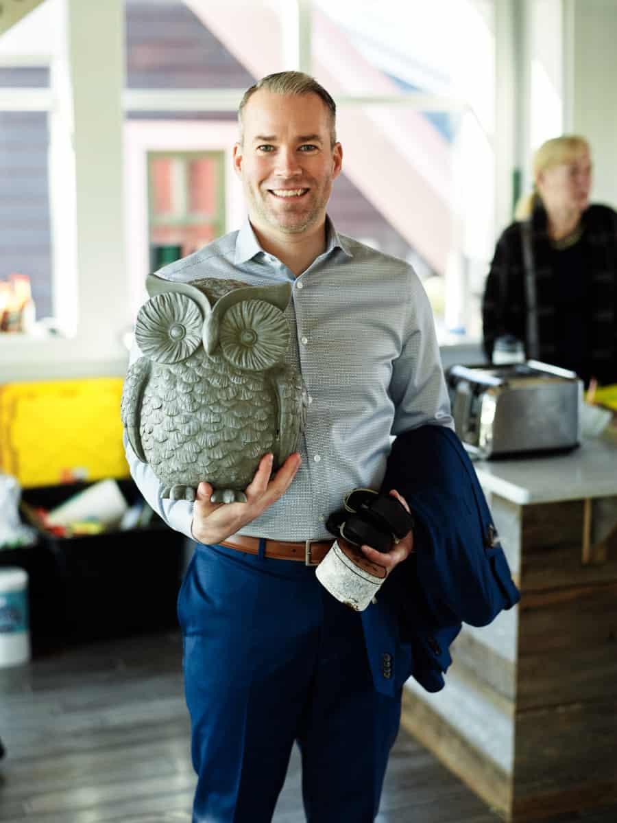 groom holding 1960's owl sculpture