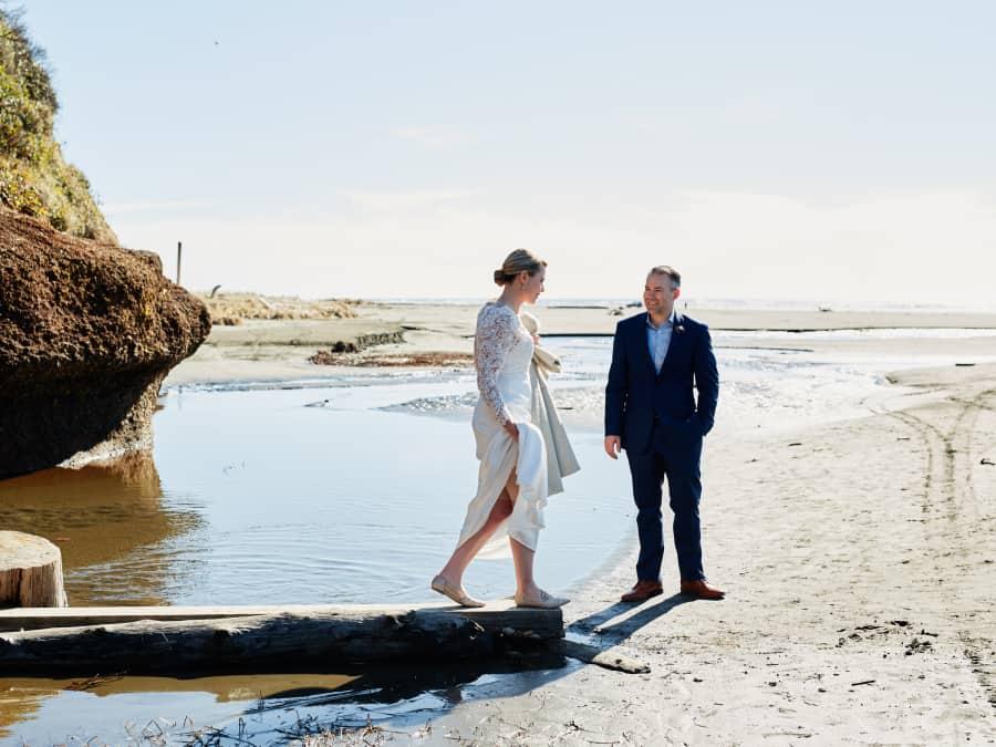bride walking over water on log bridge