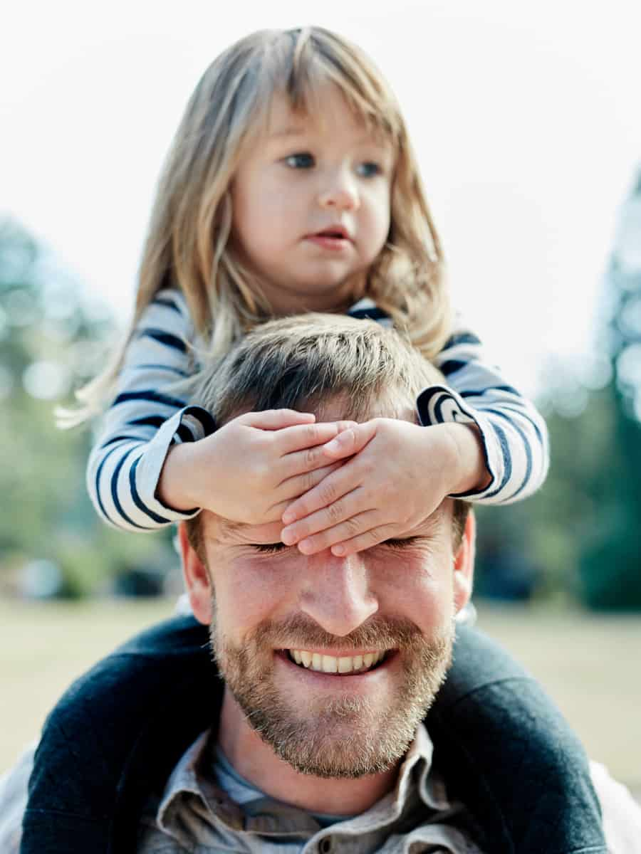 girl holding hands over dad's eyes