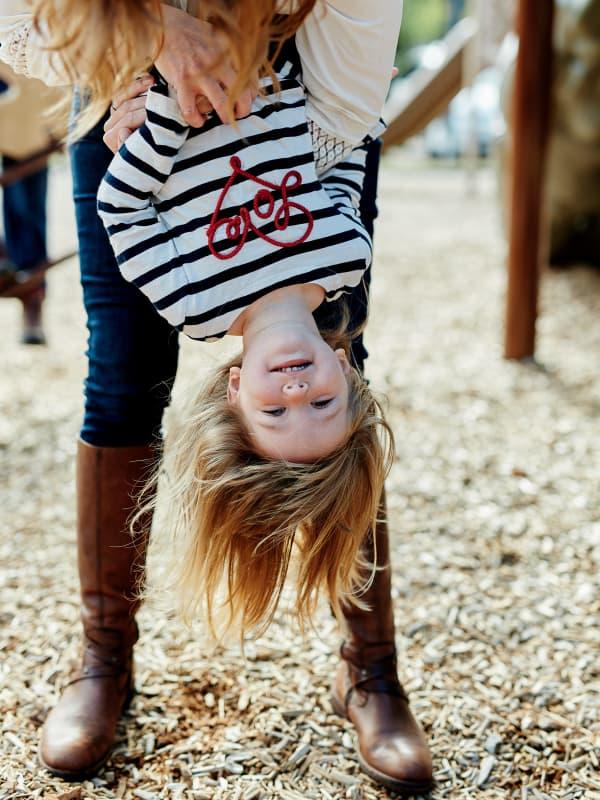 mom holding girl upside down