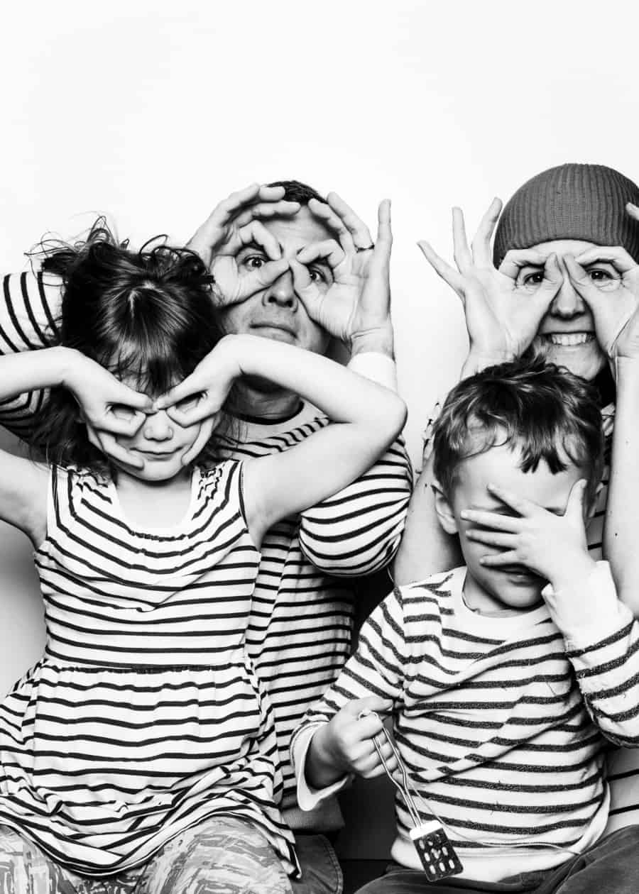 Cooper Carras in photo booth with wife and kids wearing stripes
