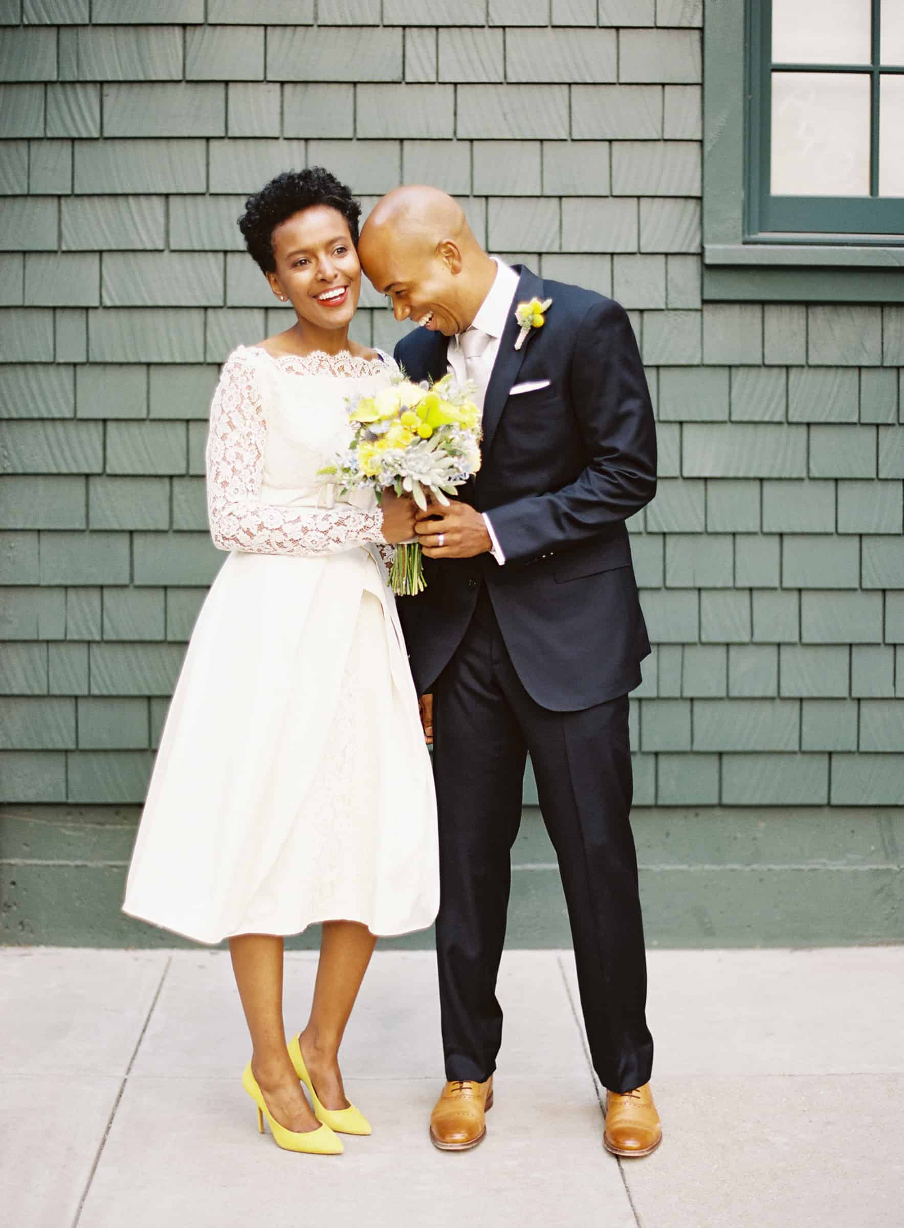 afrian american bride in short dress and groom laughing