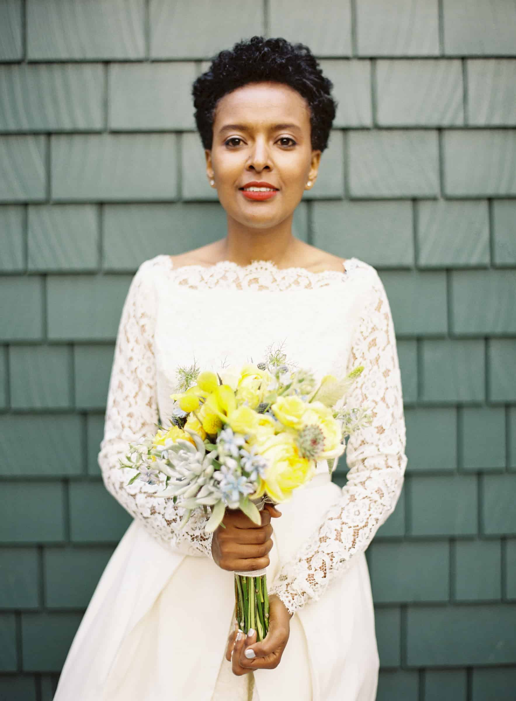 african american bride in lace dress with yellow bouquet