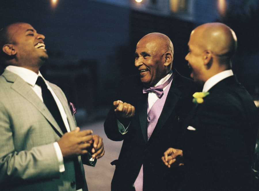 groom laughing with guests at night