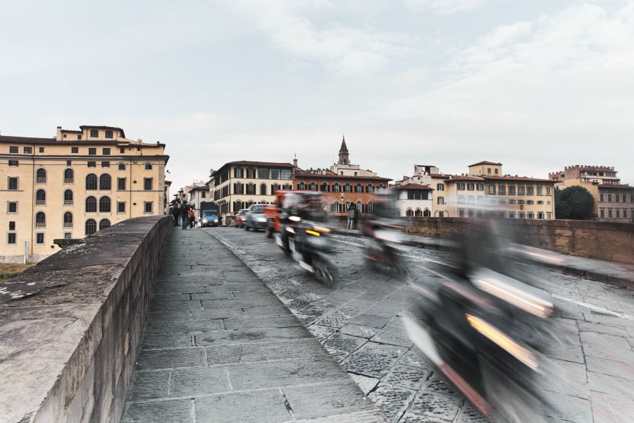 Scooters and cars crossing a bridge in Florence Italy