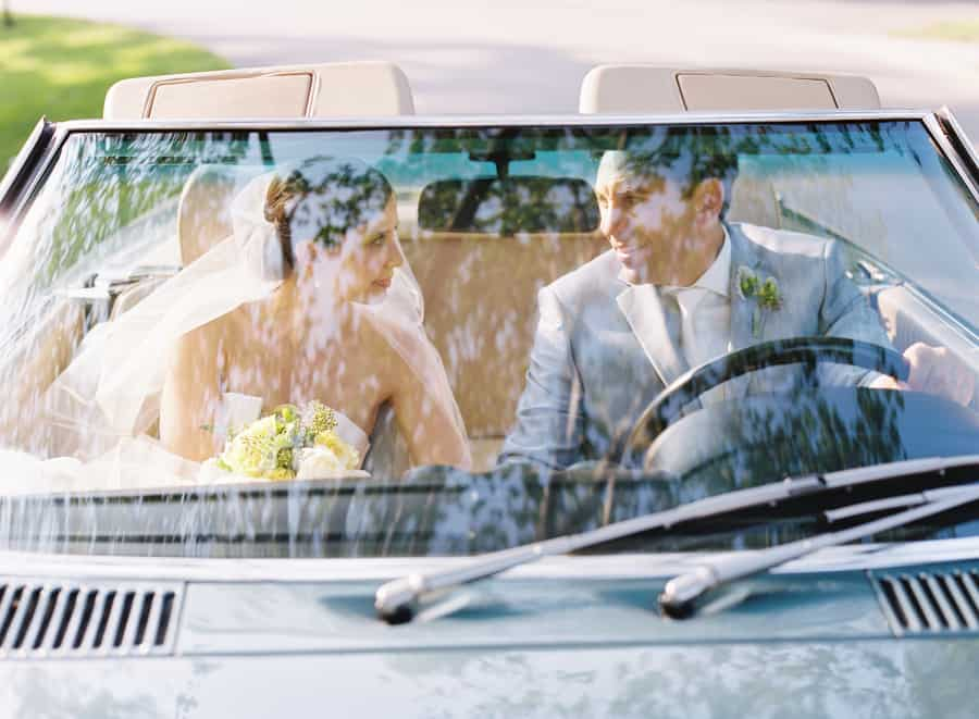 photo of married couple through vintage car window