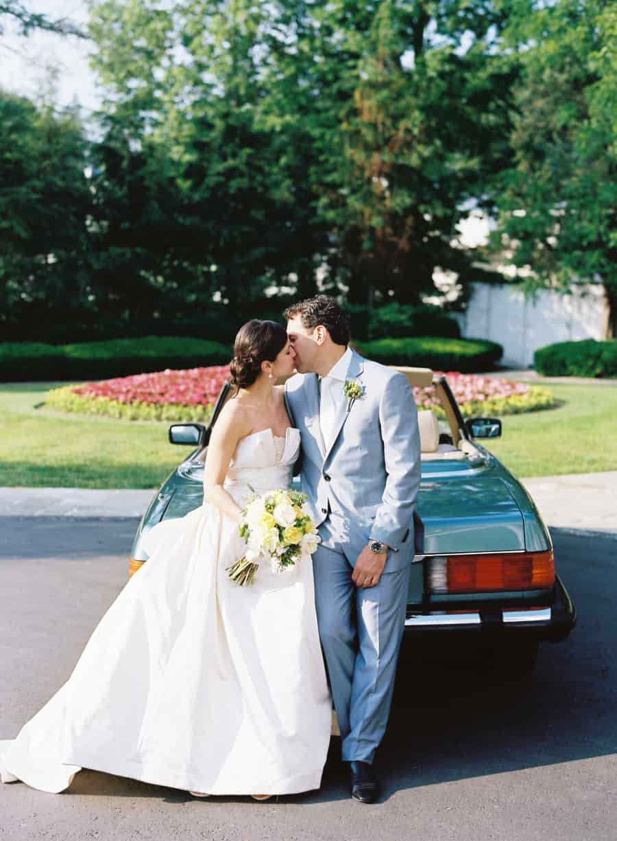 married couple kissing in front of a vintage mercedes-benz 560 SL