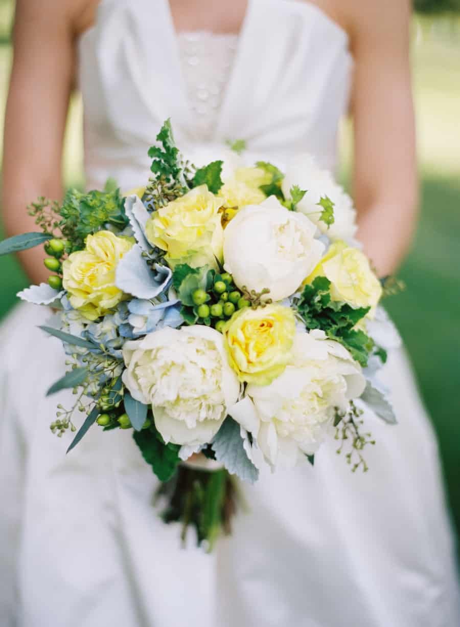 bride holding bouquet with yellow, white and blue flowers