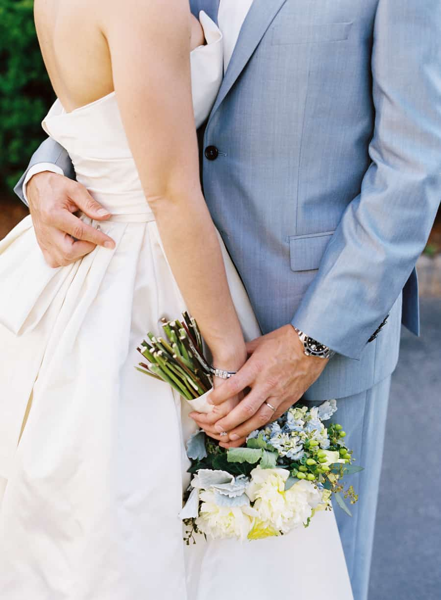 closeup of a bride in an Amsale dress and a groom in a baby blue suit holding hands