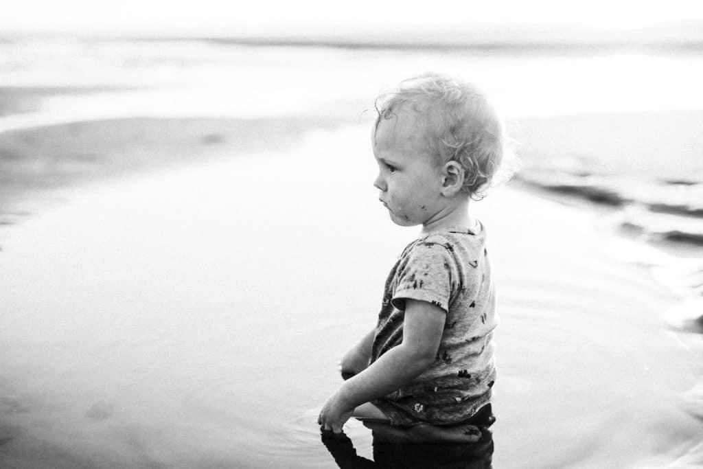 little boy playing in tide pool water at ocean