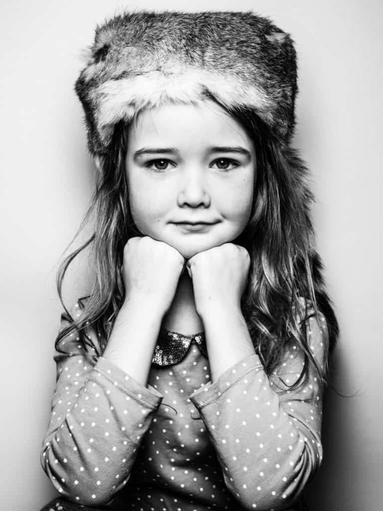 iconic kid portrait of girl in fur hat