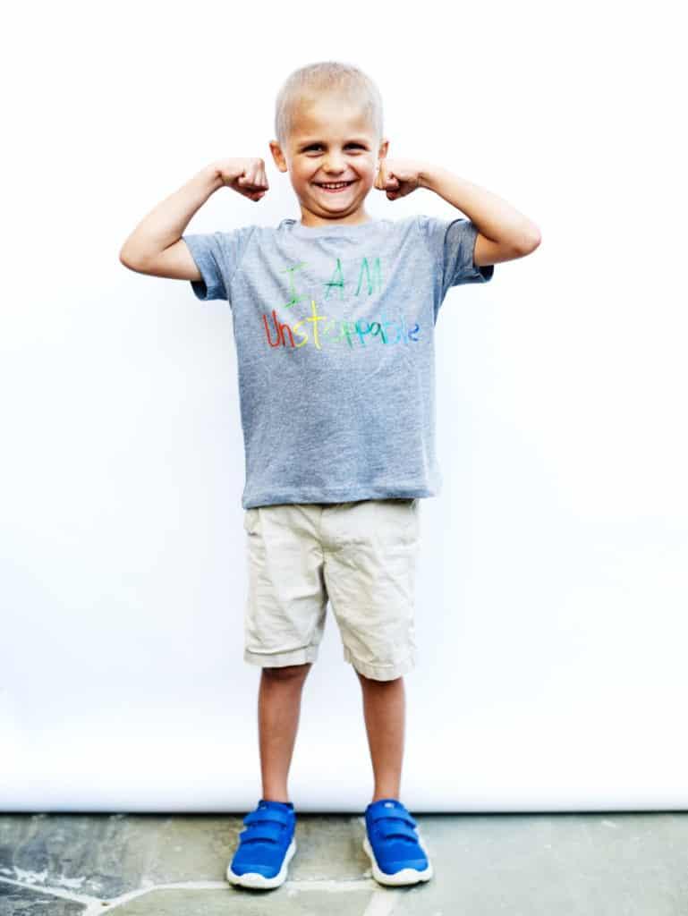 boy flexing muscles wearing inspirational shirt
