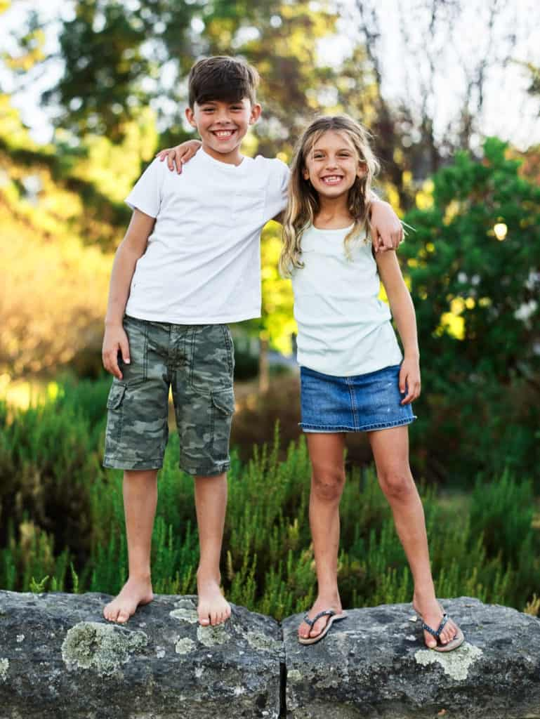 kid brother and sister standing on wall
