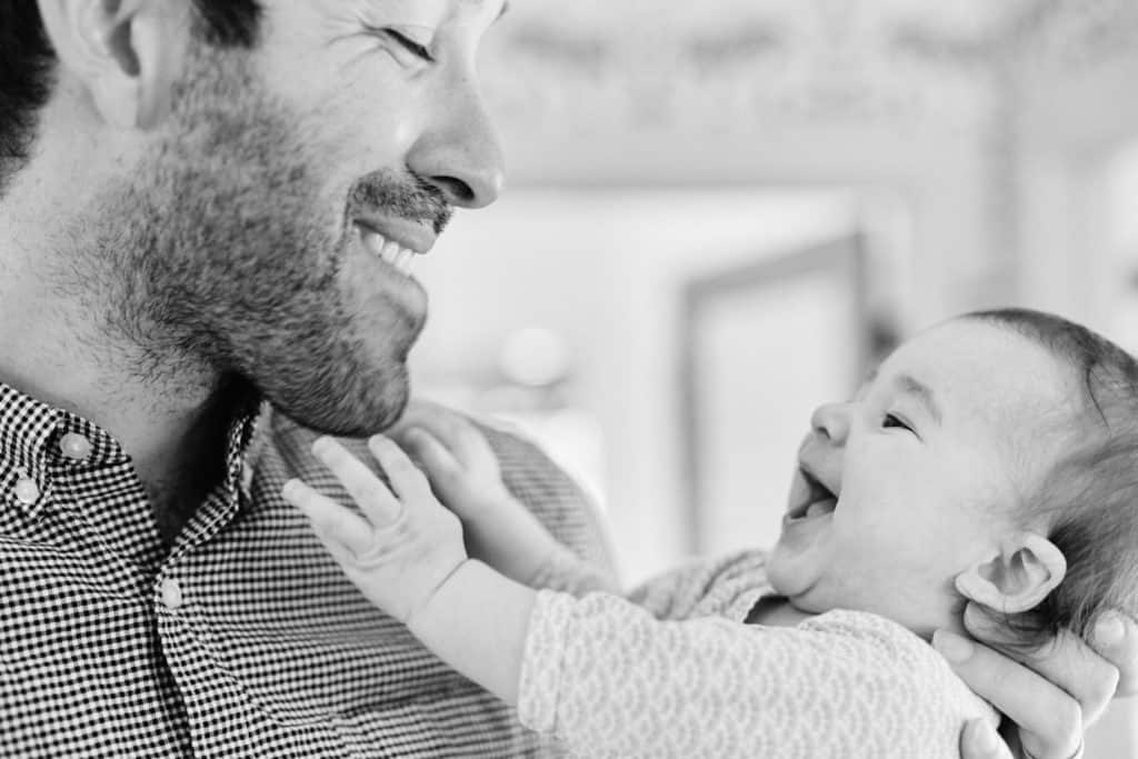 father holding laughing baby