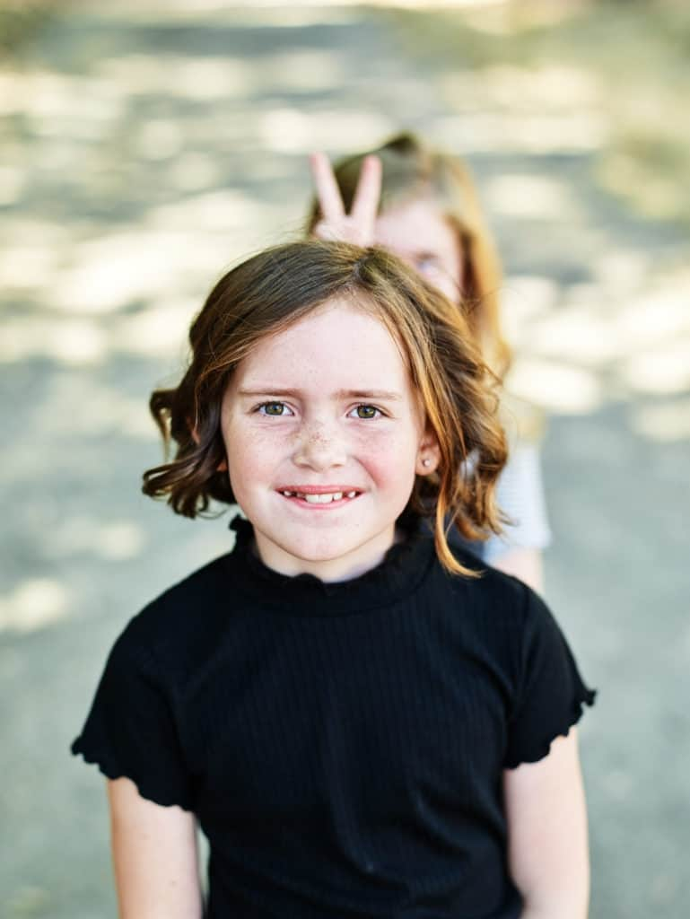 funny photo of girl getting bunny ears from sister