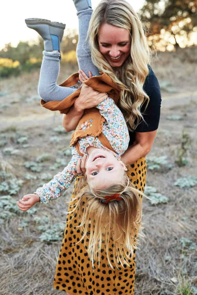 mom holding daughter upside down