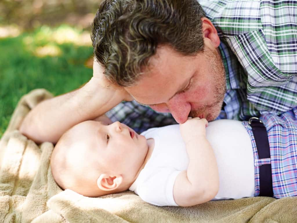 Father kissing baby on hand